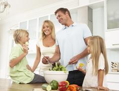 Father & Son Preparing Salad In Modern Kitchen Stock Photos