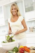 Woman Preparing Salad In Modern Kitchen Stock Photos