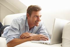 Man Using Laptop Relaxing Sitting On Sofa At Home Stock Photos