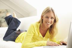 Woman Using Laptop Relaxing Sitting On Sofa At Home Stock Photos