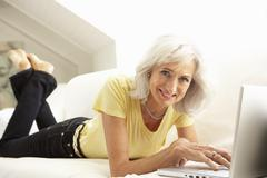 Senior Woman Using Laptop Relaxing Sitting On Sofa At Home - stock photo