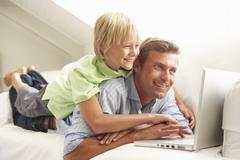 Father And Son Using Laptop Relaxing Sitting On Sofa At Home Stock Photos