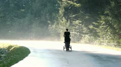 Young woman walking and pushing a baby carriage Stock Footage