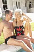 Senior Couple Relaxing by Outdoor Pool - stock photo
