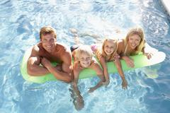 Family Outside Relaxing In Swimming Pool Stock Photos
