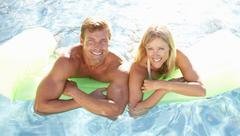 Couple Outside Relaxing In Swimming Pool - stock photo