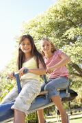 Two Girls Riding On See Saw In Playground Stock Photos