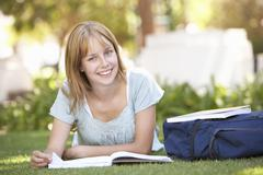 Female Teenage Student Studying In Park - stock photo