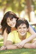 Portrait Of  Romantic Teenage Couple Sitting In Park Stock Photos