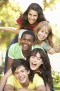 Group Of Teenagers Piled Up In Park Stock Photos