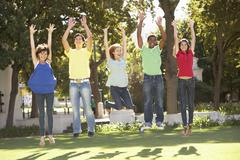 Group Of Teenagers Jumping In Air In Park Stock Photos