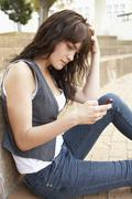 Unhappy Female Teenage Student Sitting Outside On College Steps Using Mobile Stock Photos