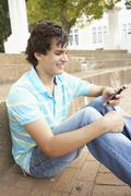 Male Teenage Student Sitting Outside On College Steps Using Mobile Phone - stock photo