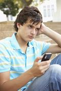 Unhappy Male Teenage Student Sitting Outside On College Steps Using Mobile Phone - stock photo