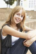 Smiling Teenage Student Sitting Outside On College Steps - stock photo