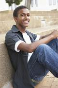 Smiling Male Teenage Student Sitting Outside On College Steps - stock photo