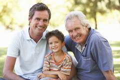 Grandfather With Father And Son In Park - stock photo