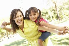 Mother Giving Daughter Ride On Back In Park - stock photo