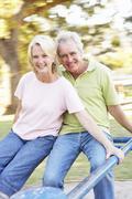 Senior Couple Riding On Roundabout In Park Kuvituskuvat
