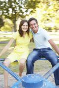 Young Couple Riding On Roundabout In Park Stock Photos