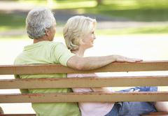 Senior Couple Sitting Together On Park Bench Stock Photos