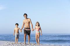 Father Running With Children Along Sandy Beach Stock Photos