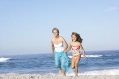 Grandmother Running With Granddaughter Along Sandy Beach - stock photo