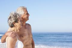 Senior Couple On Holiday Walking Along Sandy Beach - stock photo