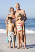 Grandparents And Grandchildren Standing On Sandy Beach Stock Photos