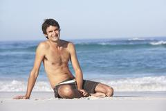 Young ManWearing Swimwear Sitting On Sandy Beach Stock Photos