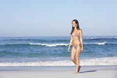 Young Woman Walking Along Sandy Beach On Holiday Wearing Bikini - stock photo