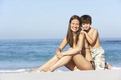 Mother And Son Relaxing Together On Beach Holiday - stock photo