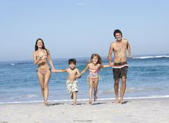 Young Family Running Along Beach on Holiday - stock photo