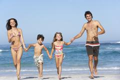 Young Family Running Along Beach on Holiday Stock Photos