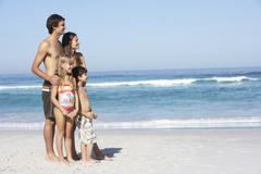 Young Family Standing On Sandy Beach on Holiday - stock photo