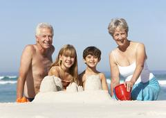 Grandparents And Grandchildren Building Sandcastles Together On Beach Holiday - stock photo