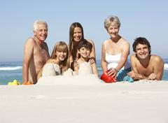 Three Generation Family Building Sandcastles On Beach Holiday - stock photo