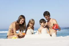 Family Building Sandcastles On Beach Holiday - stock photo