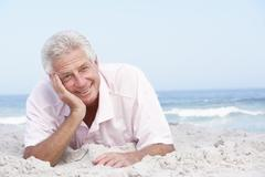 Senior Man Relaxing On Sandy Beach - stock photo