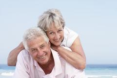 Senior Couple Relaxing On Beach Holiday - stock photo