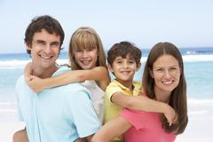 Family Having Piggyback Fun On Beach Holiday Stock Photos