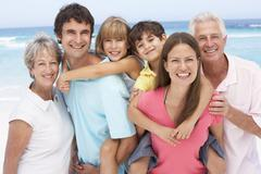 Three Generation Family Relaxing On Beach Holiday - stock photo