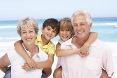 Grandparents And Grandchildren Relaxing On Beach Holiday Stock Photos