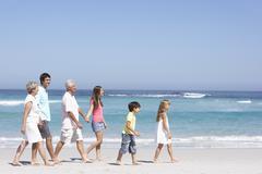 Three Generation Family Walking Along Sandy Beach Stock Photos