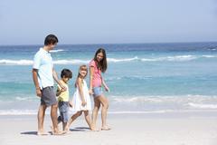 Family Walking Along Sandy Beach Stock Photos
