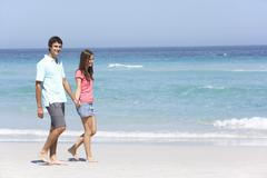 Couple On Holiday Walking Along Sandy Beach - stock photo