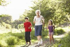 Grandmother Jogging In Park With Grandchildren - stock photo