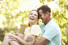 Young Couple In Walking Clothes Resting On Tree In Park Stock Photos