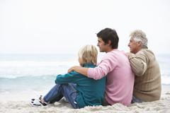 Grandfather, Father And Grandson Sitting On Winter Beach Stock Photos