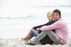 Young Couple On Holiday Sitting On Winter Beach Stock Photos